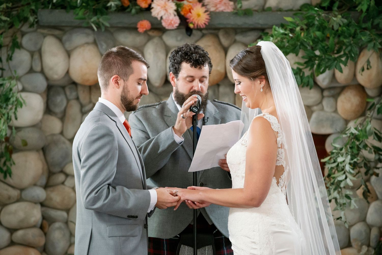 groom places ring on brides hand during ceremony