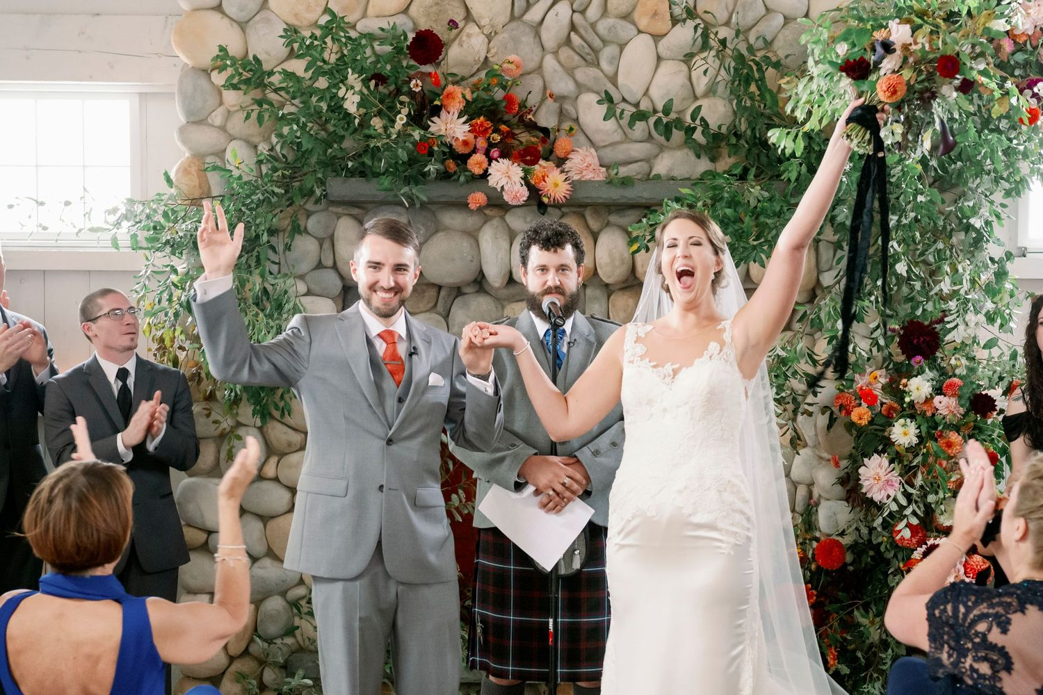 bride and groom raise hands in celebration at Bonnet Island Estate