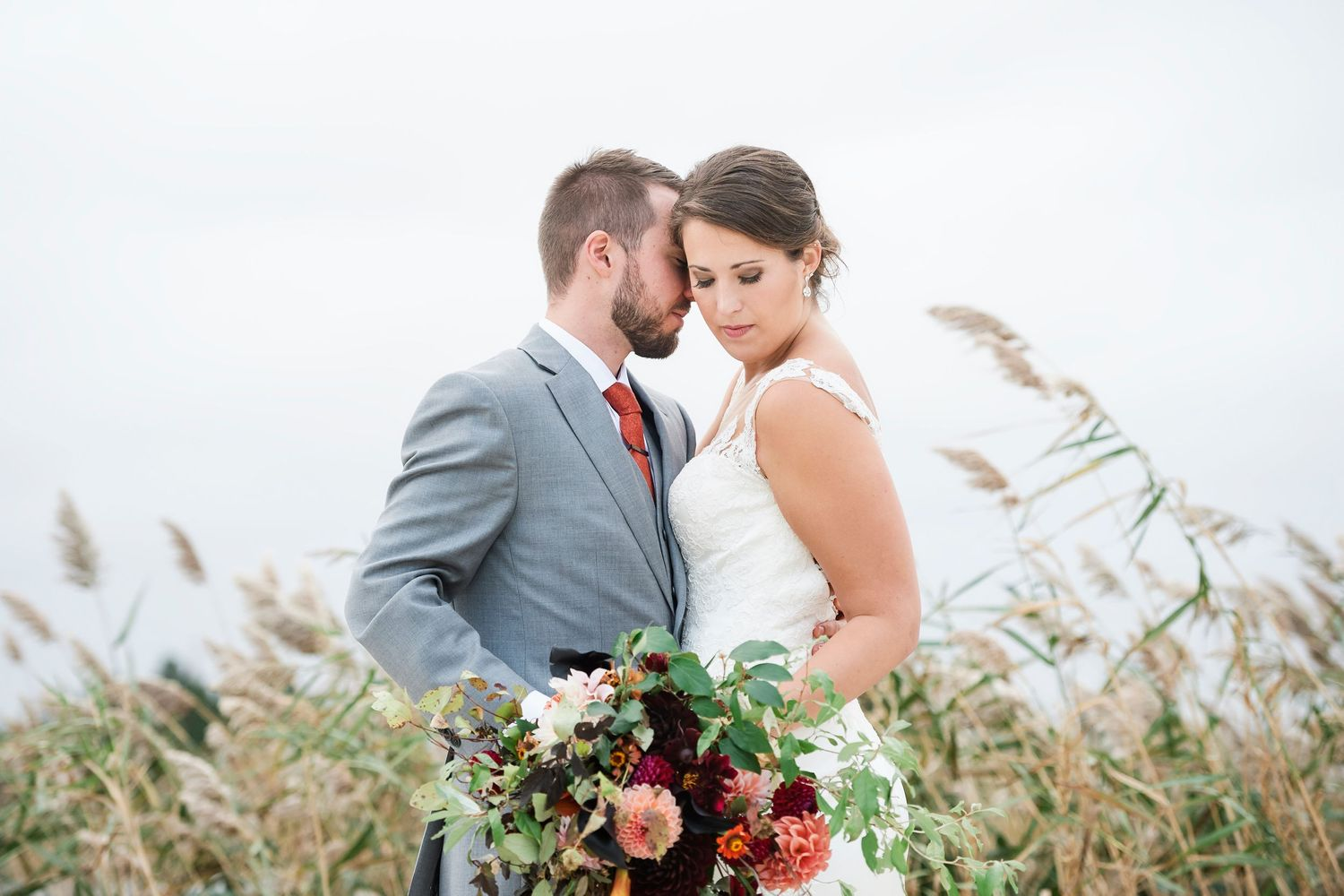 groom nuzzles bride with dune grass behind them at Bonnet Island Estate