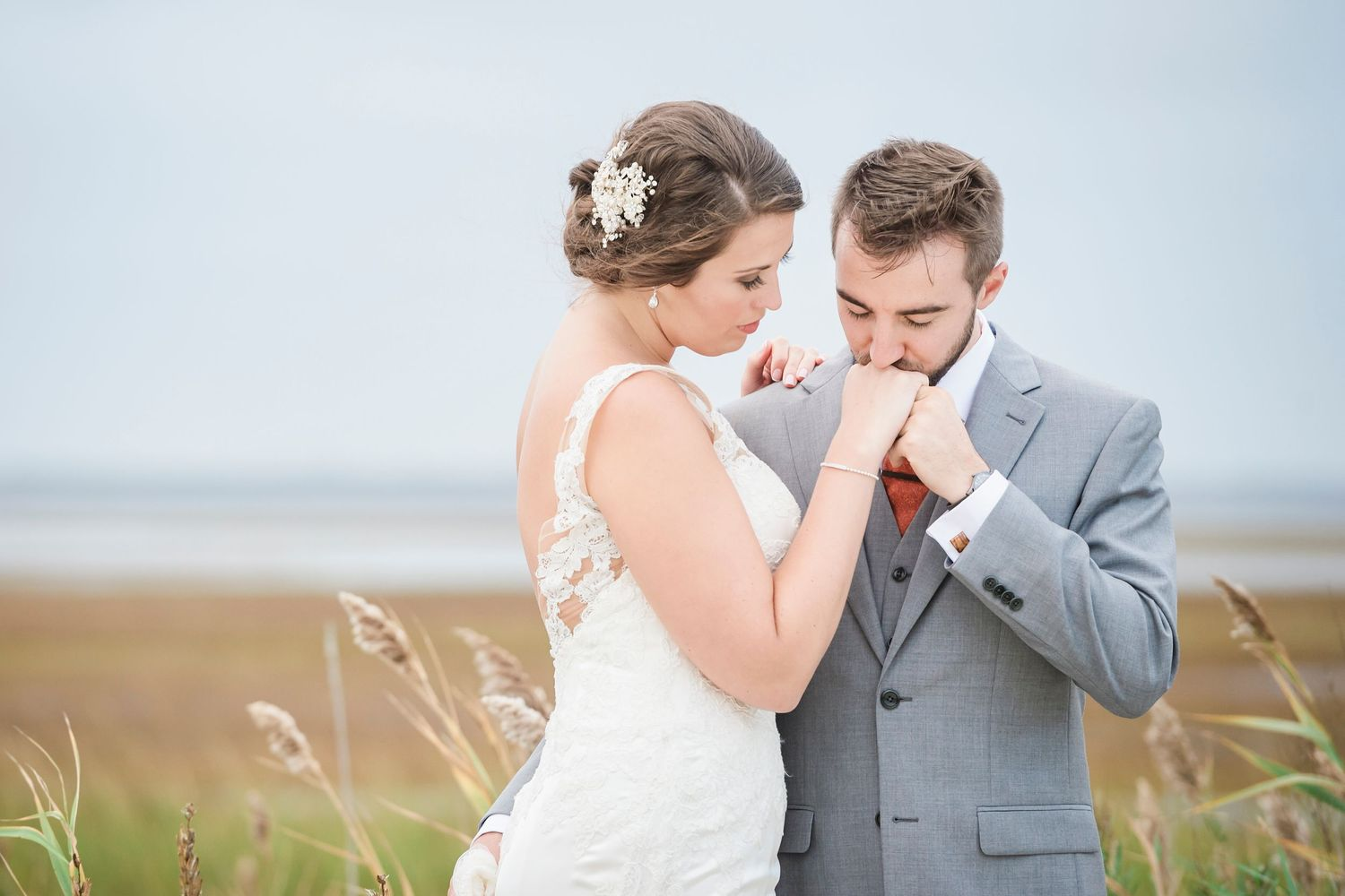 tight shot of groom kissing brides hand at Bonnet Island Estate