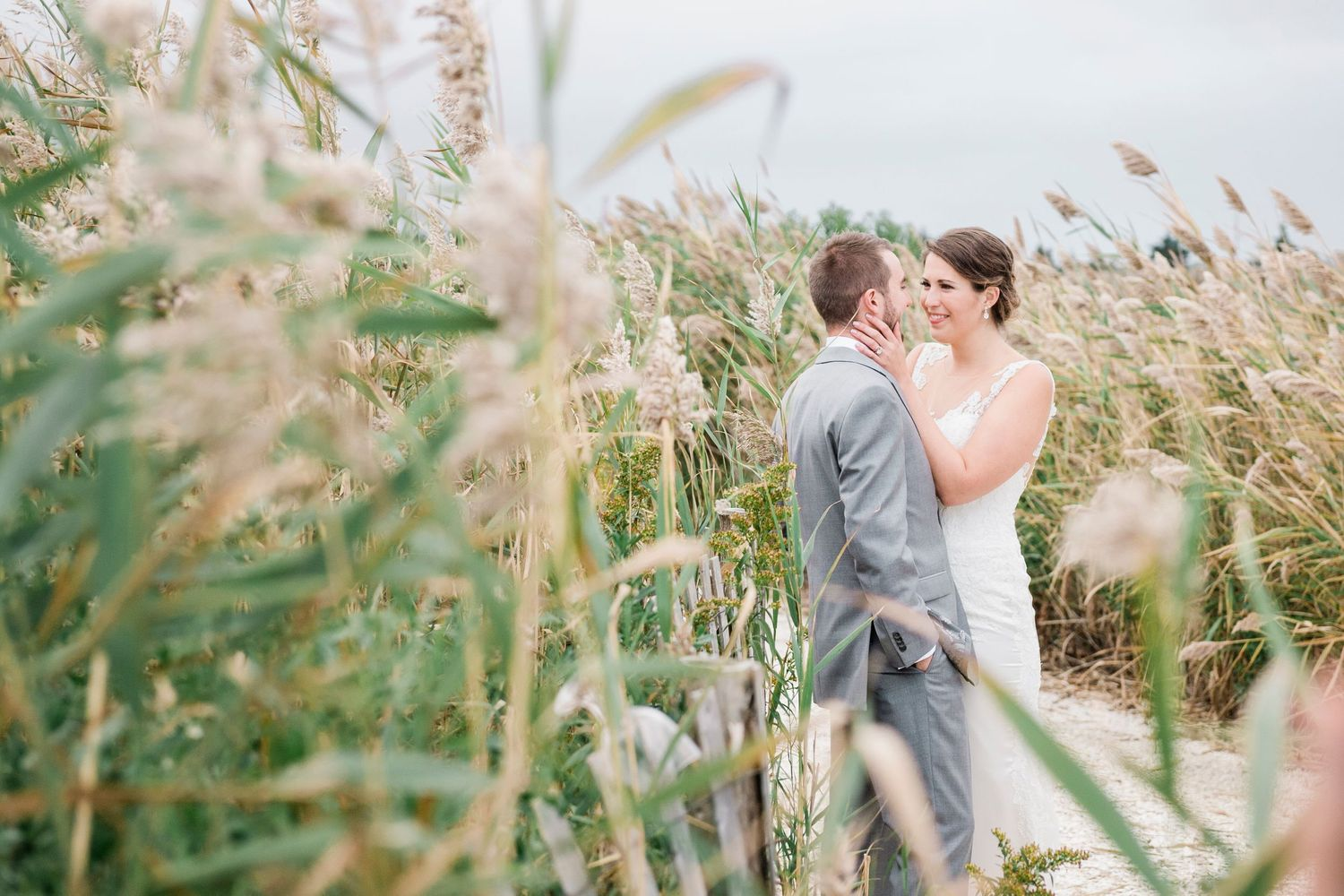 bride and groom photograph through the dune grass