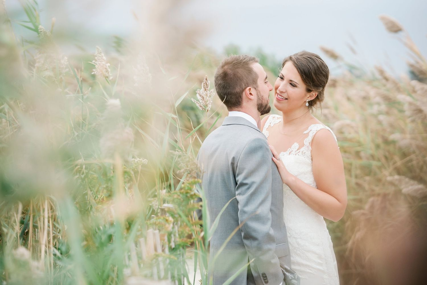 bride looks and groom lovingly shot through grass