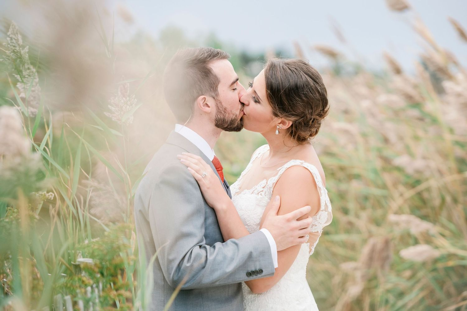 bride and groom kiss amongst the reeds at Bonnet Island Estate