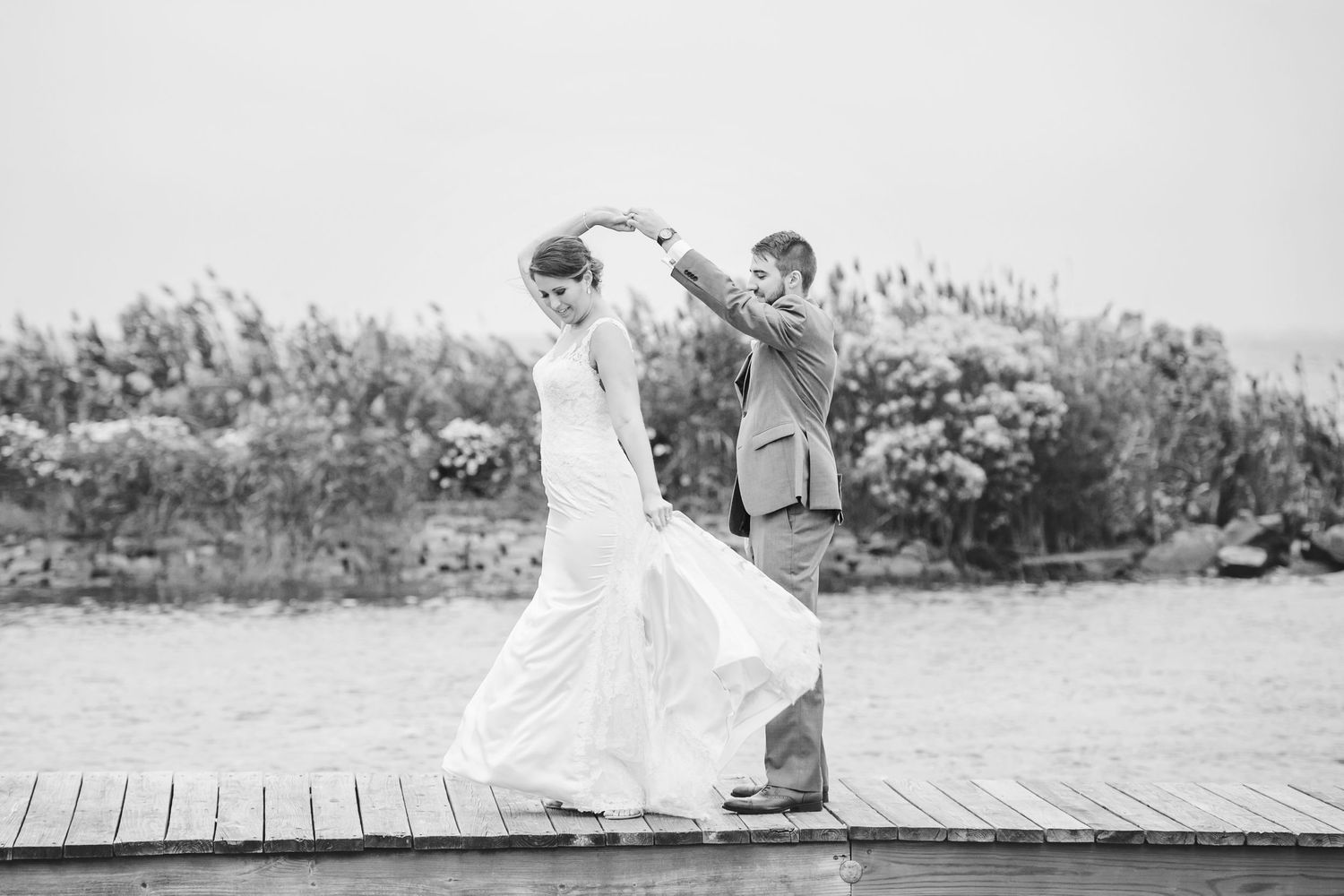 groom twirls bride on dock at Bonnet Island Estate