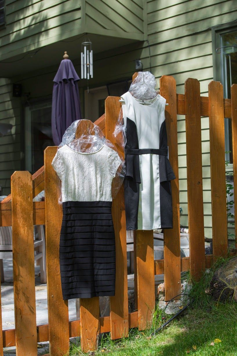 Two bride's dresses hanging on a wooden fence