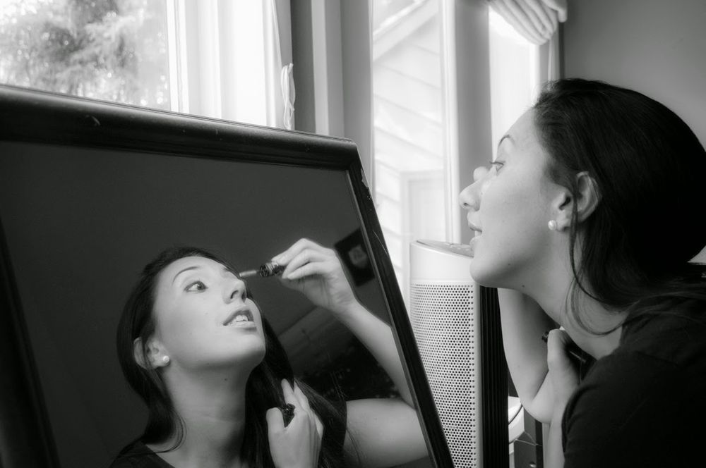 Bride getting ready, looking in mirror, black and white