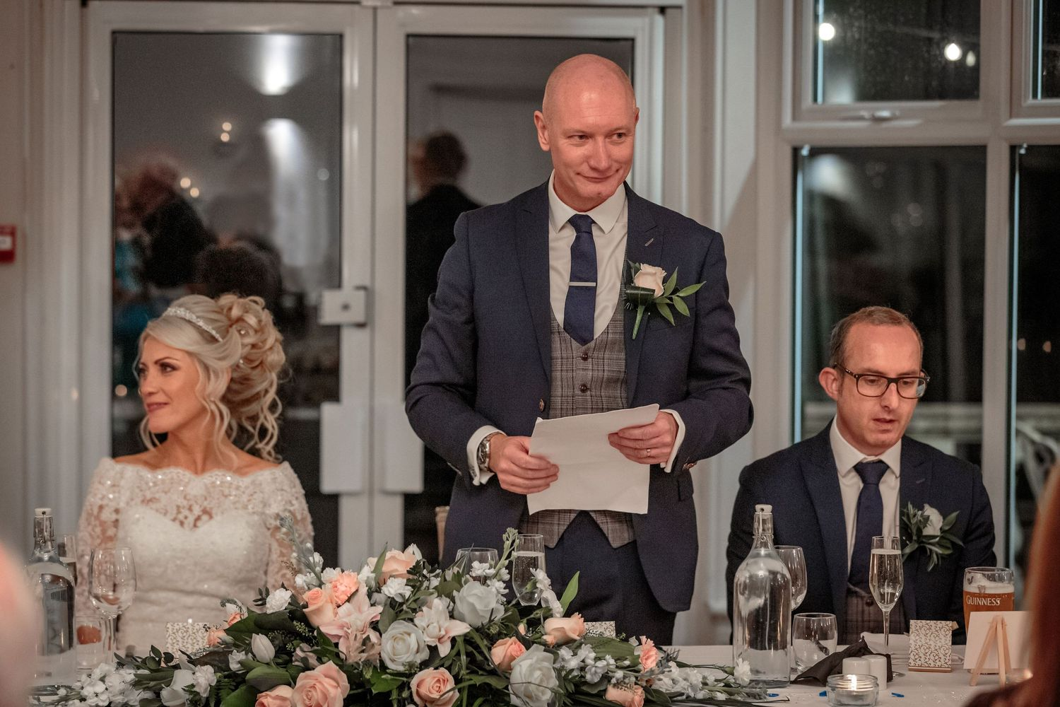 the groom stands up holding his notes to give his wedding speech