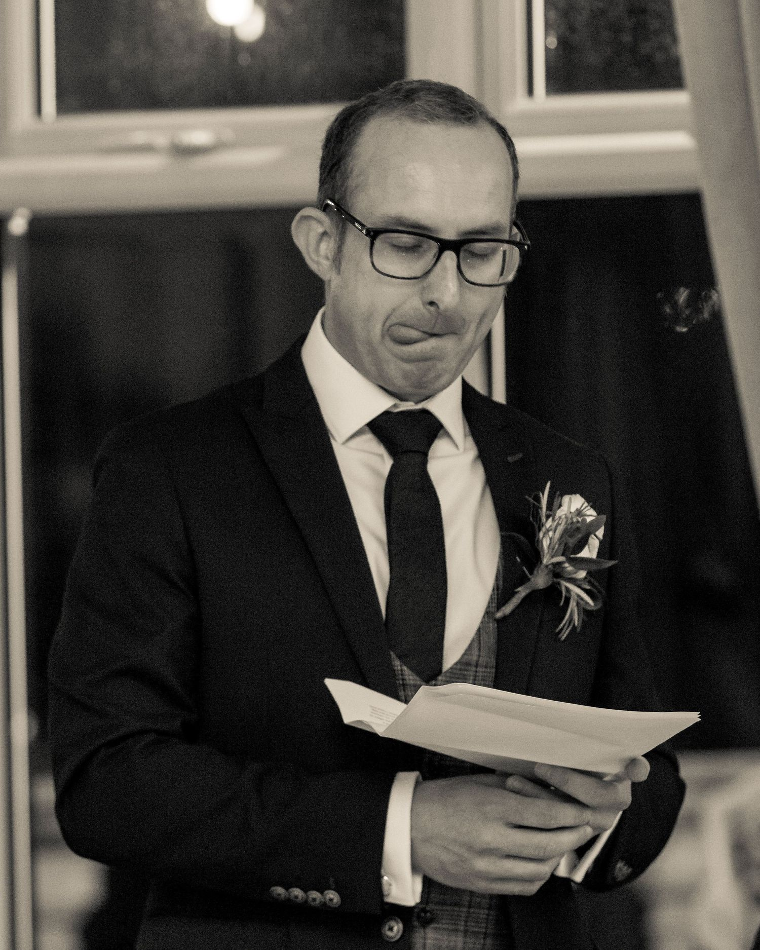 the best man holding his notes with his tongue out while giving his wedding speech