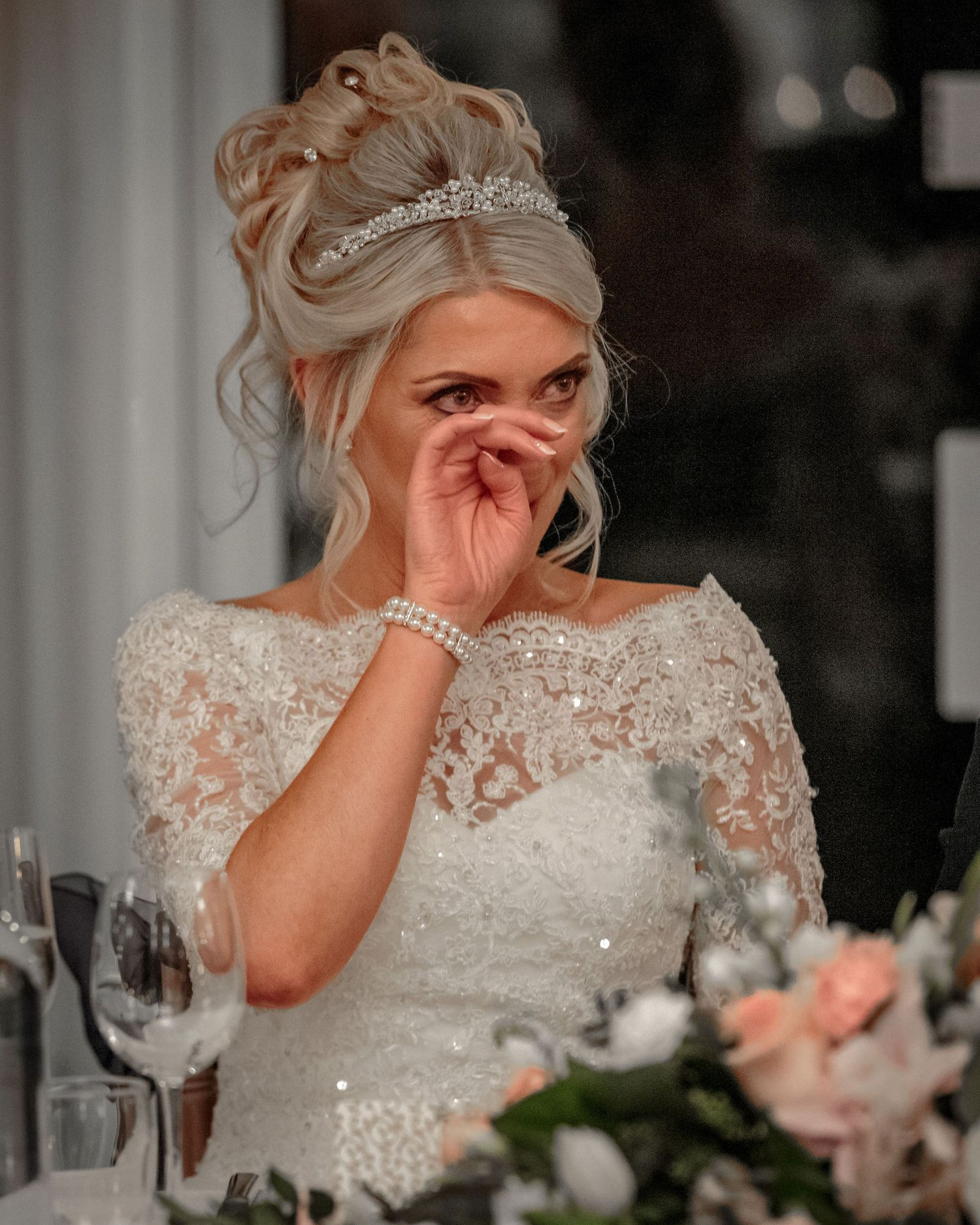 bride puts her hand to her face to wipe away a tear during the wedding speeches