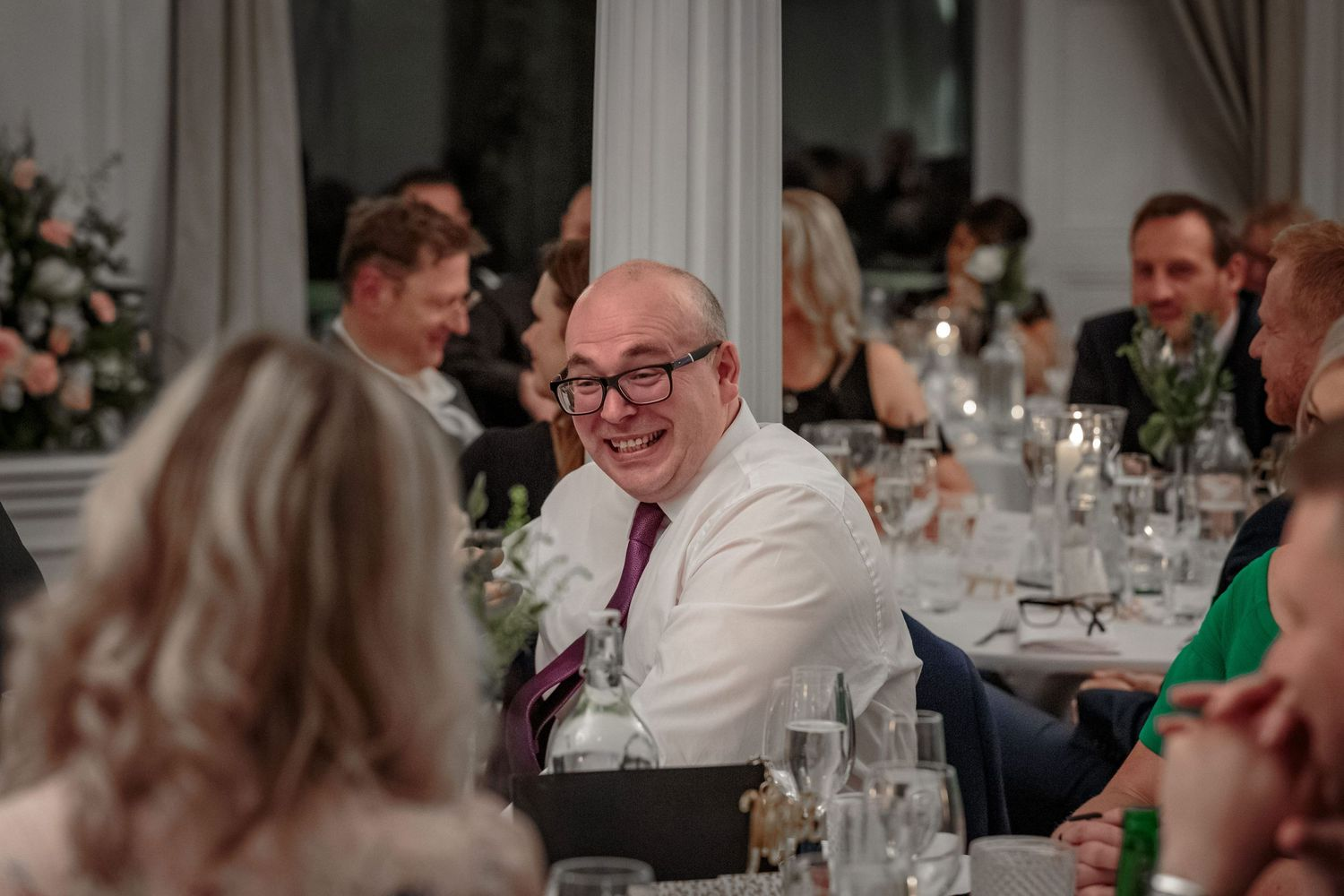 wedding guest laughing as the best man recounts the stag do during his speech