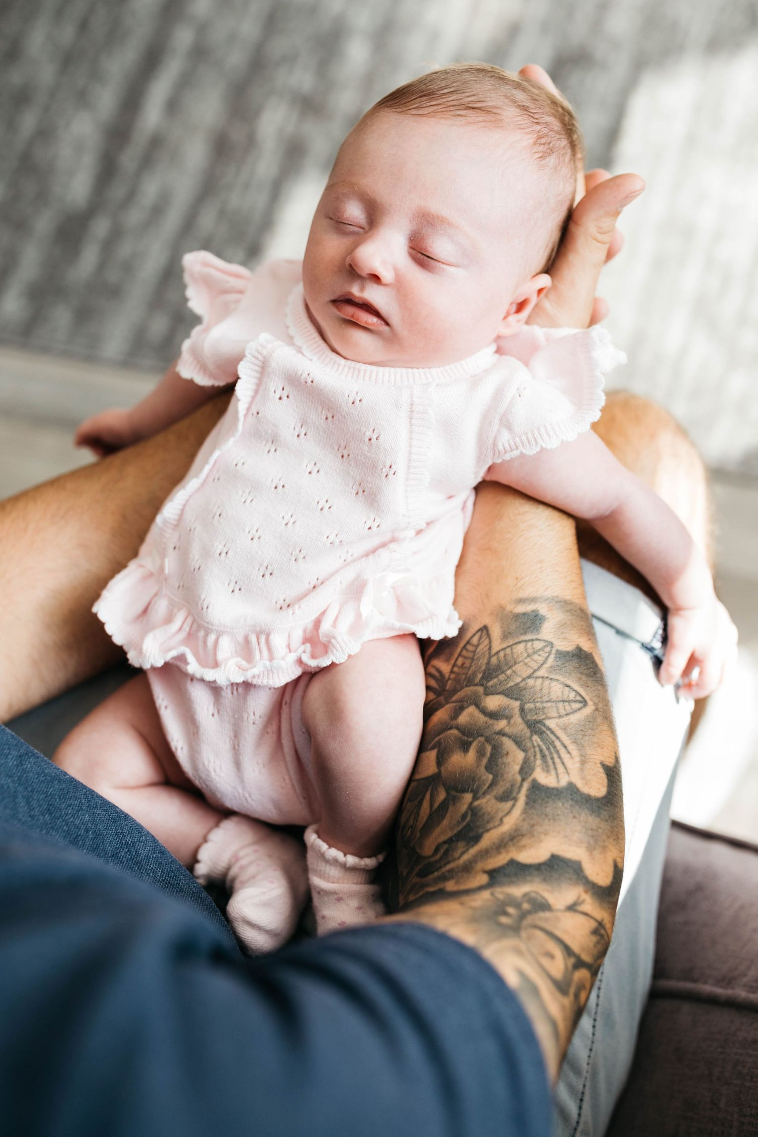 tiny newborn baby girl sleeping in dad arms