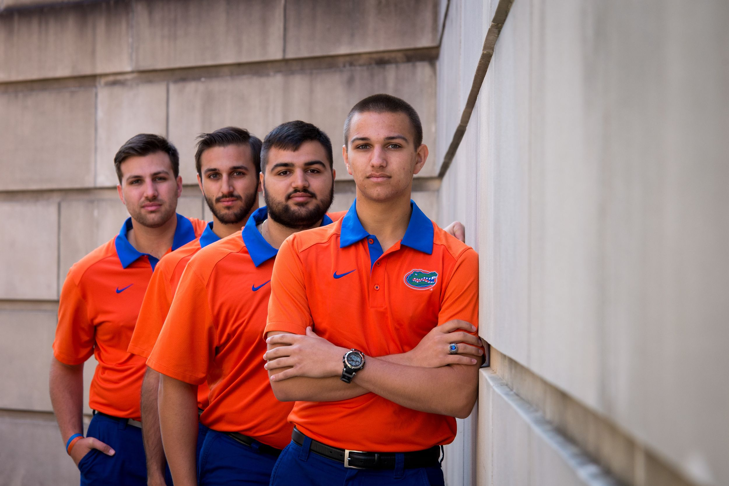 Four brothers dress in orange and blue pose for a portrait at the University of Florida in Gainesville, Fl.