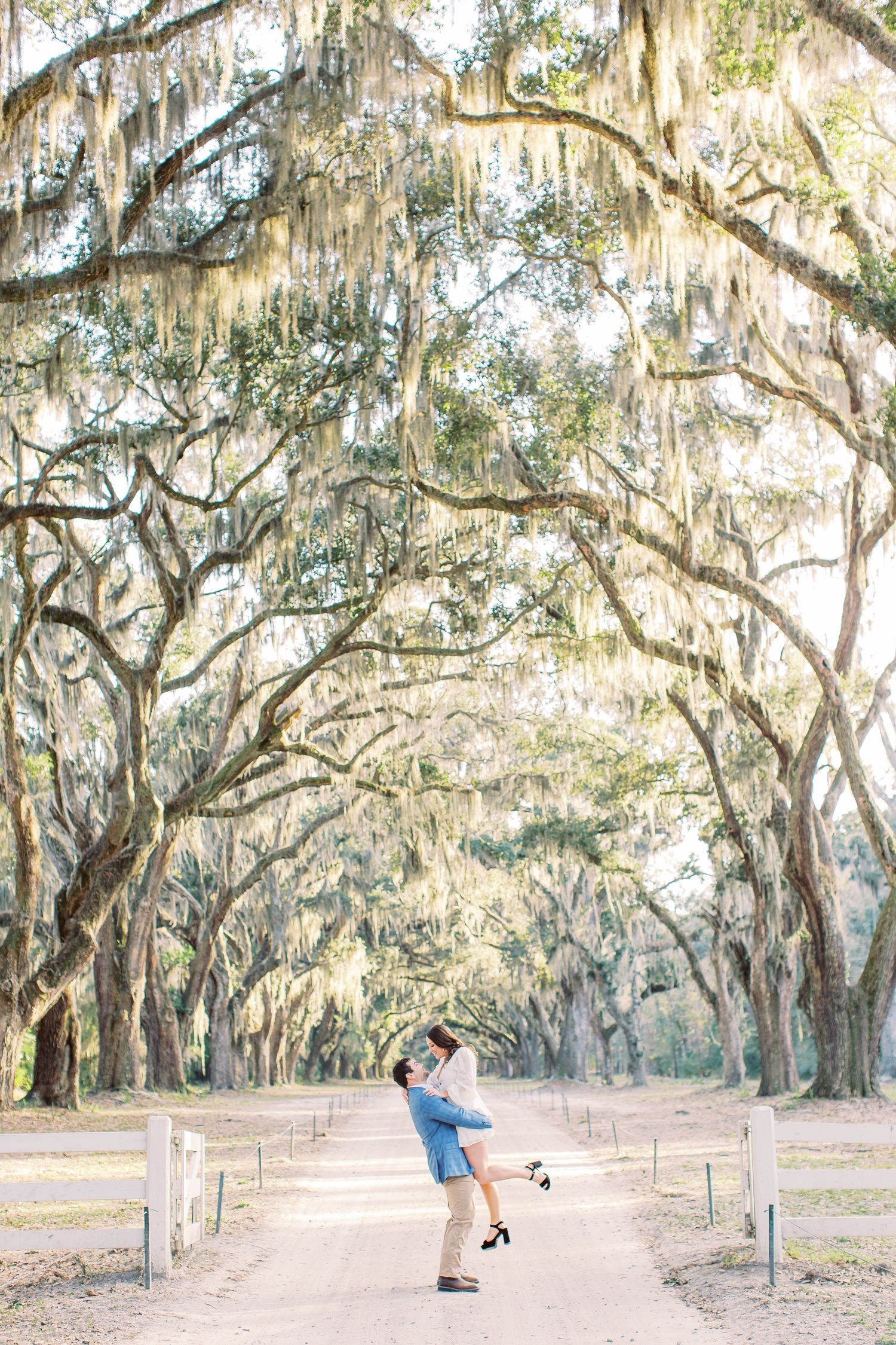 guy lifts girl during engagement session at wormsloe in savannah, ga