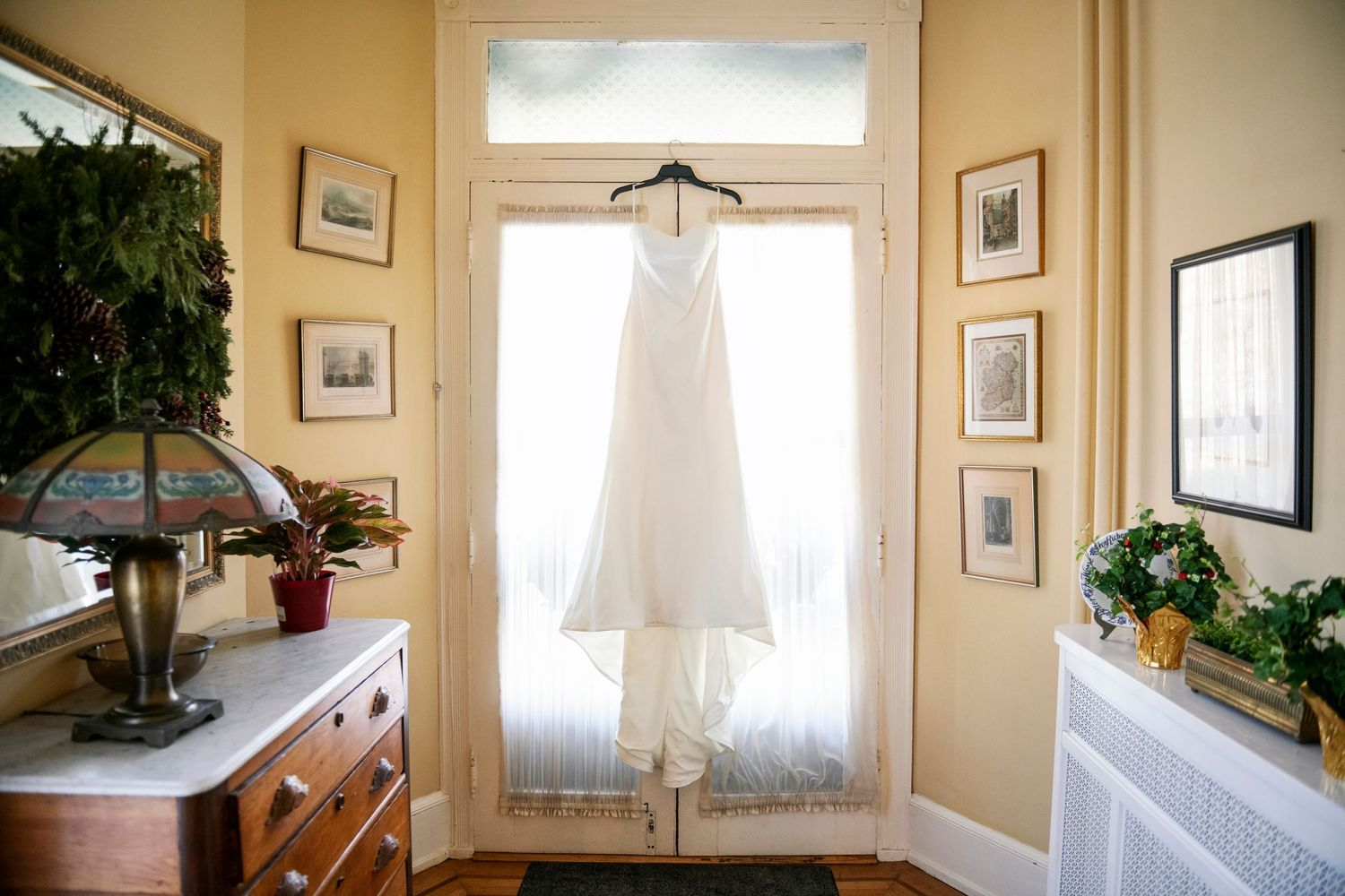 bride's dress hanging in door way