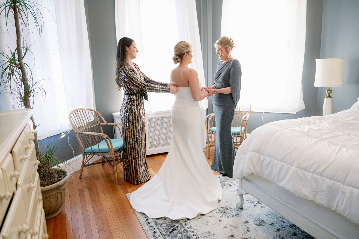 bride getting dressed with help from sister and mom