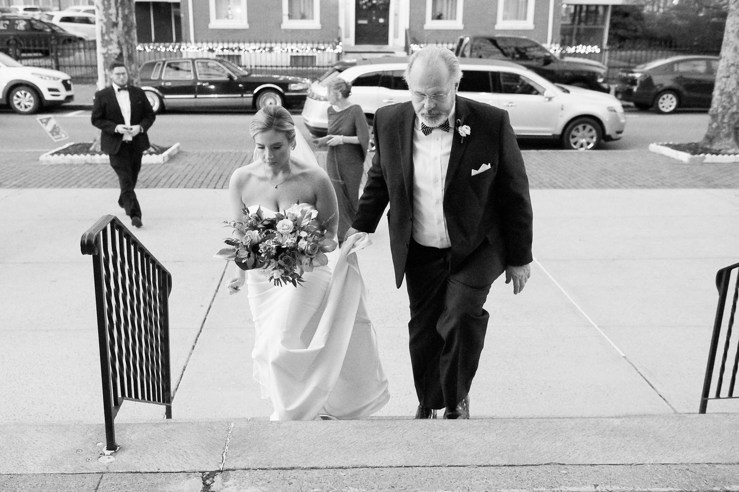 bride's father escorting her up the church steps