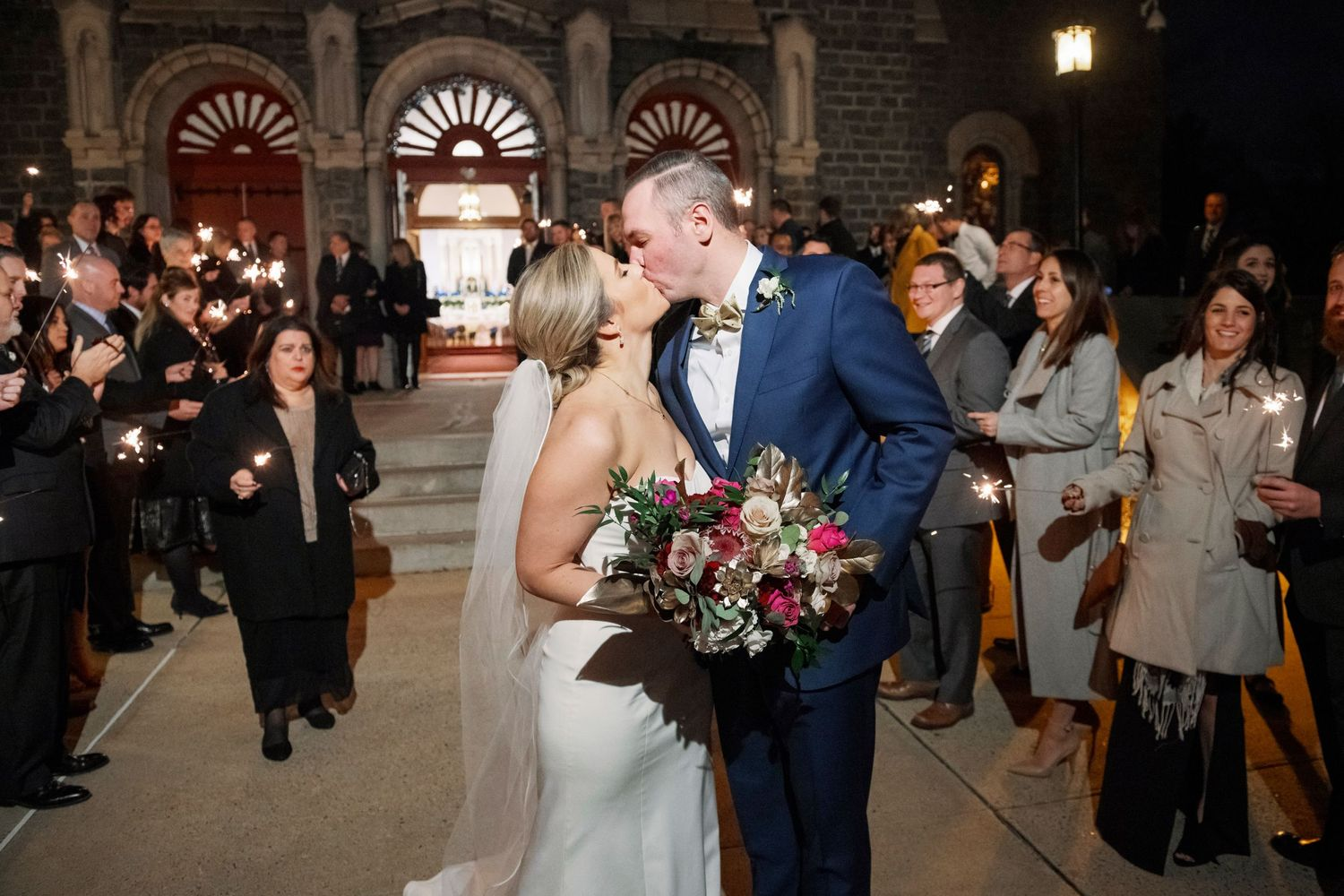 bride and groom kiss during sparkler exit at church
