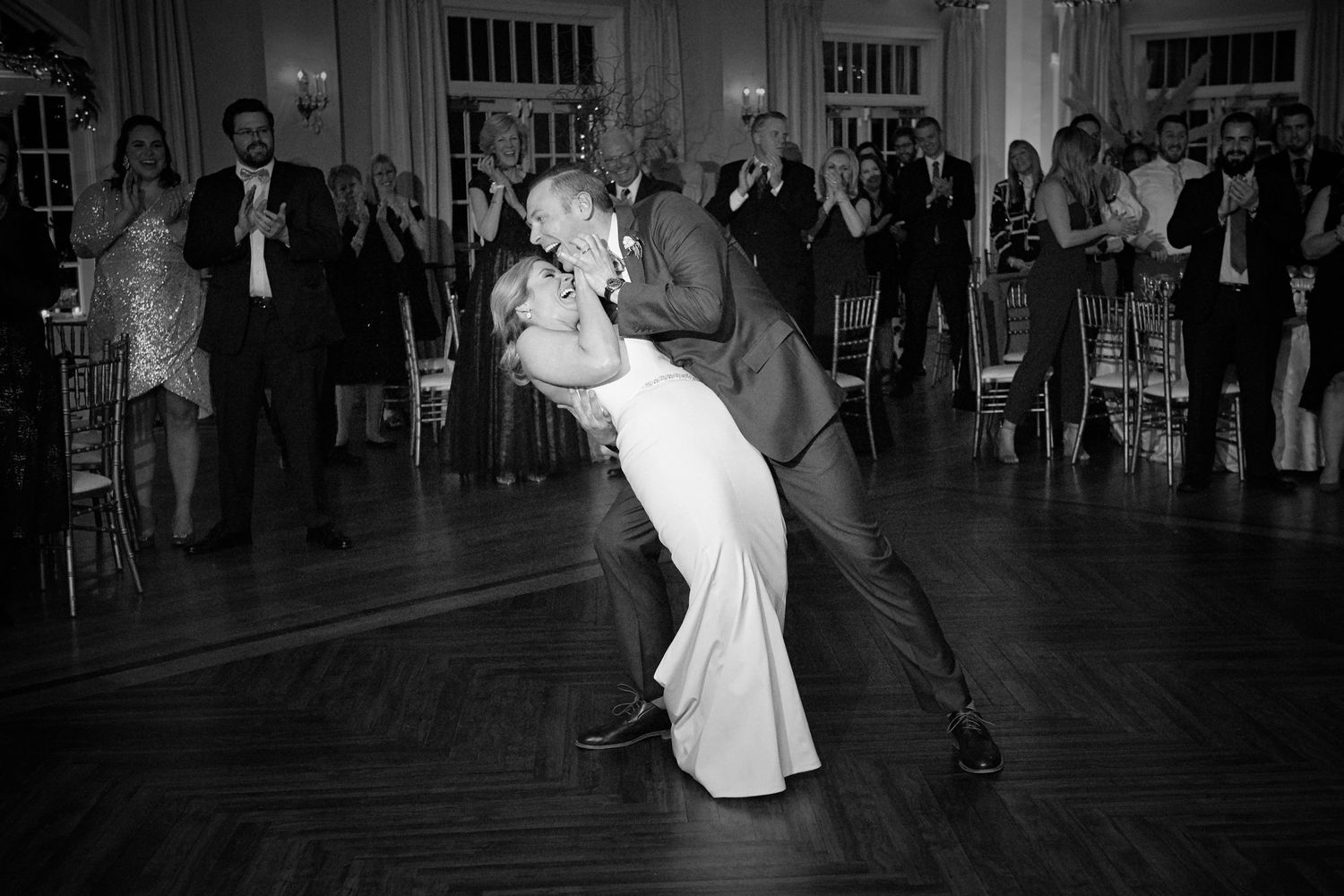 groom dips the bride on the dance floor during first dance at Belle Voir Manor