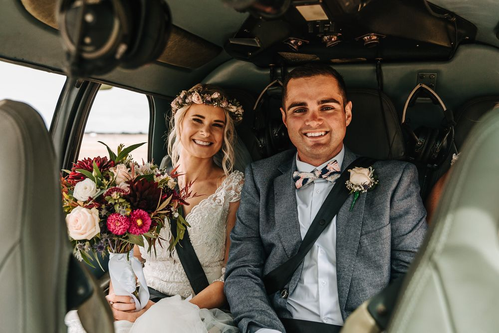 Bride and groom in helicopter with bouquet