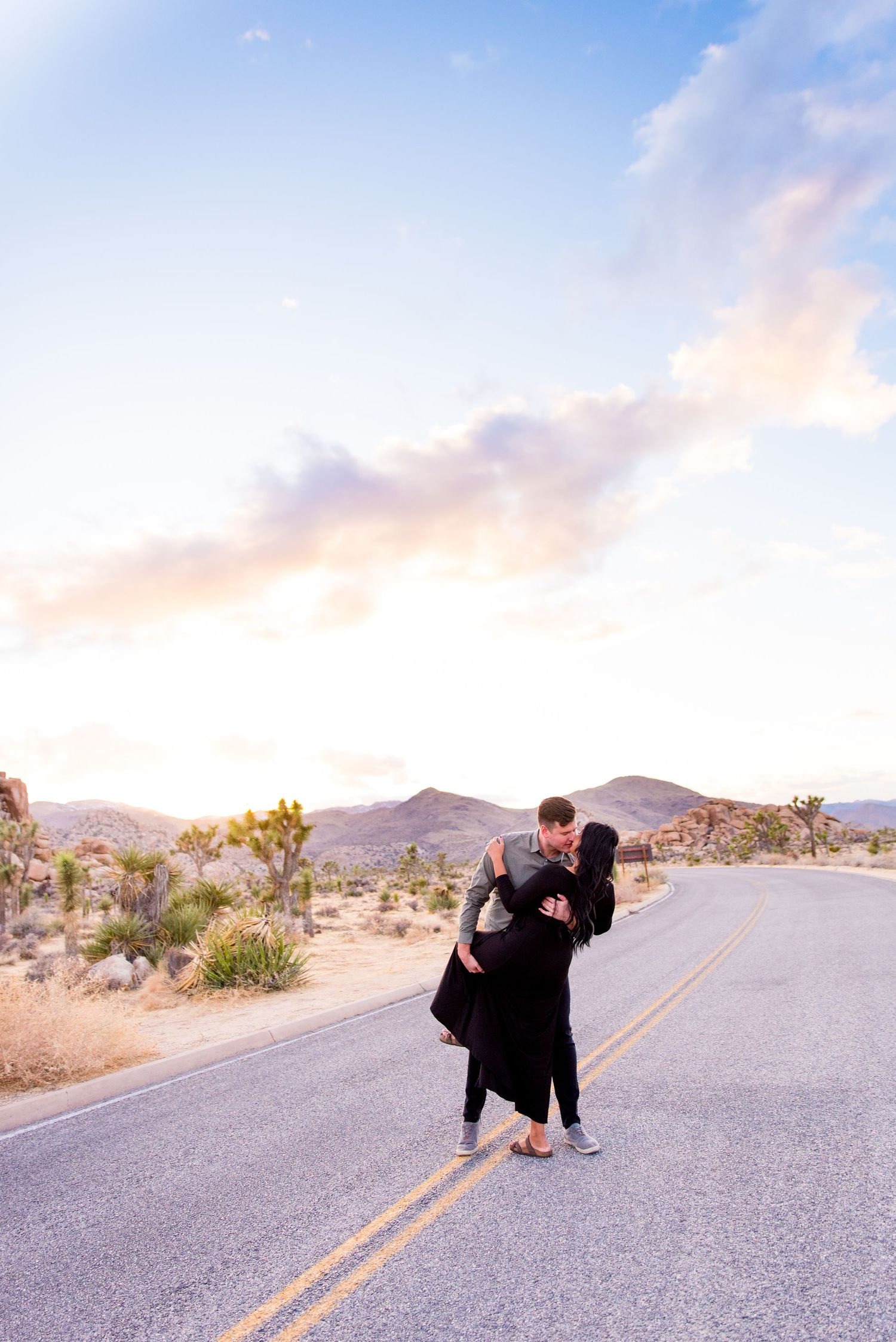 man in gray shirt dips his fiancee in black dress in the middle of the road during sunset at Joshua Tree National Park