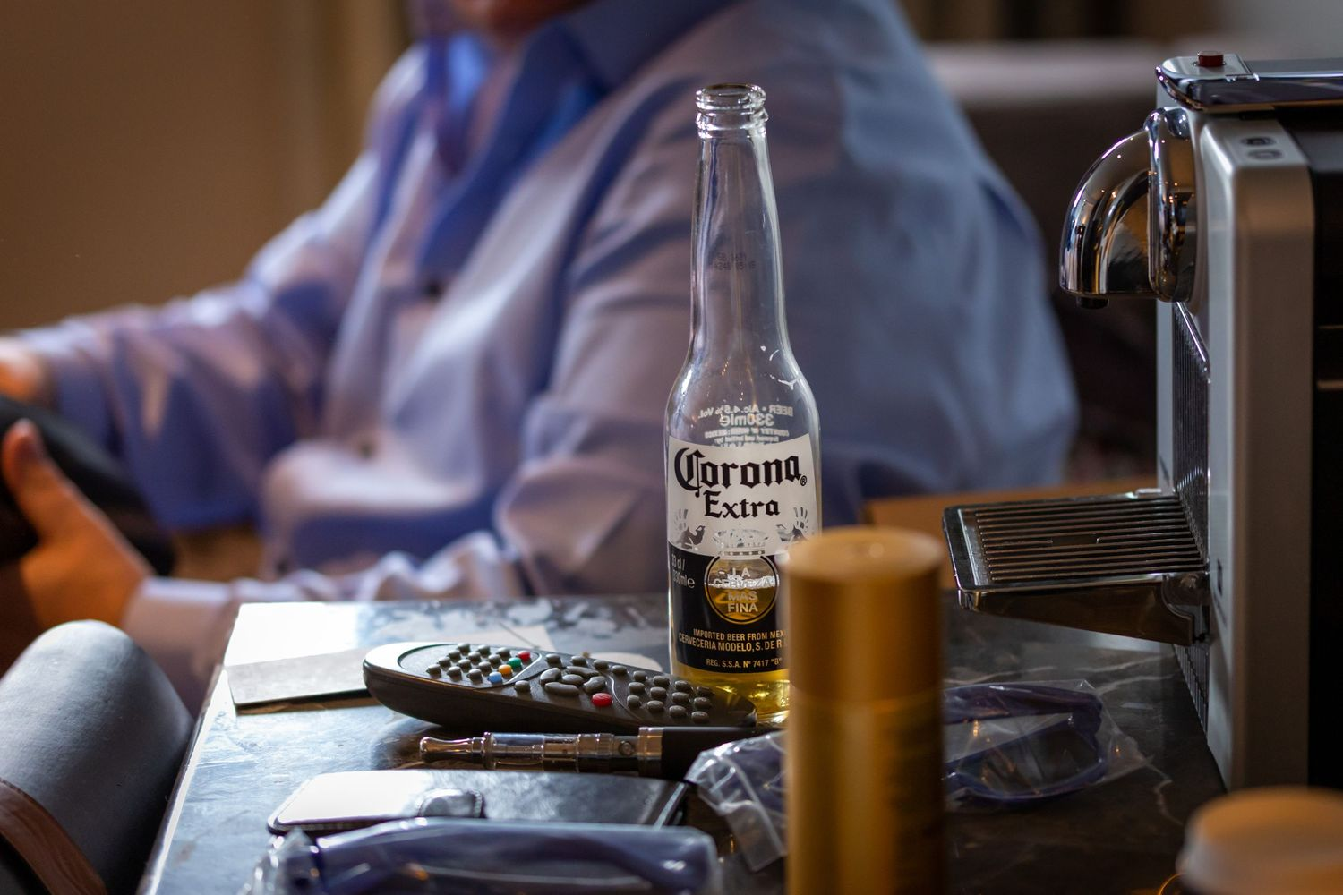 half empty bottle of corona larger on the side table during the groom prep at the vincent hotel southport covid wedding