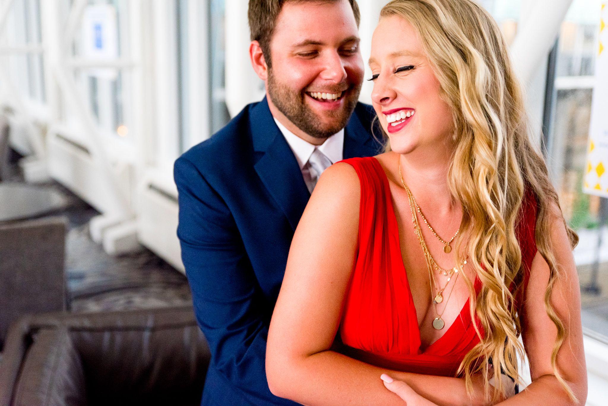 couple in red dress and navy suit laughing inside the Galt House Hotel for engagement pictures