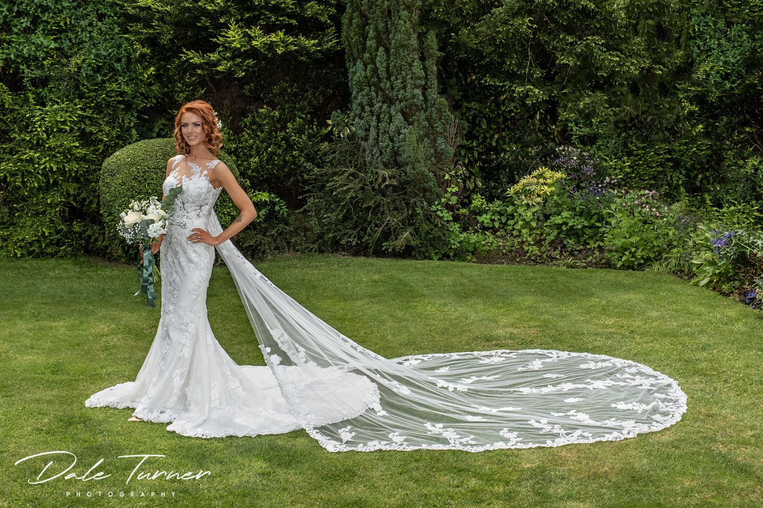 Beautiful bride posing on her own in garden on wedding day