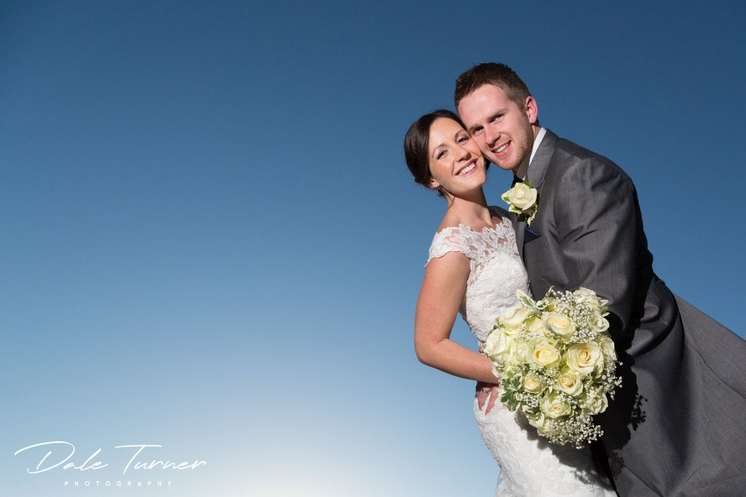 Bride and groom with big blue sky