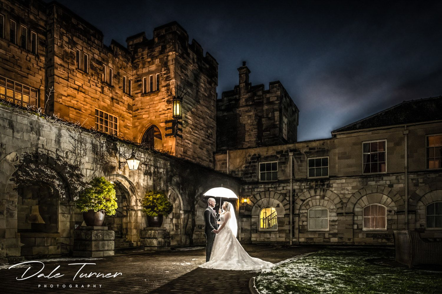 Hazlewood Castle at night with bride and groom holding umbrella