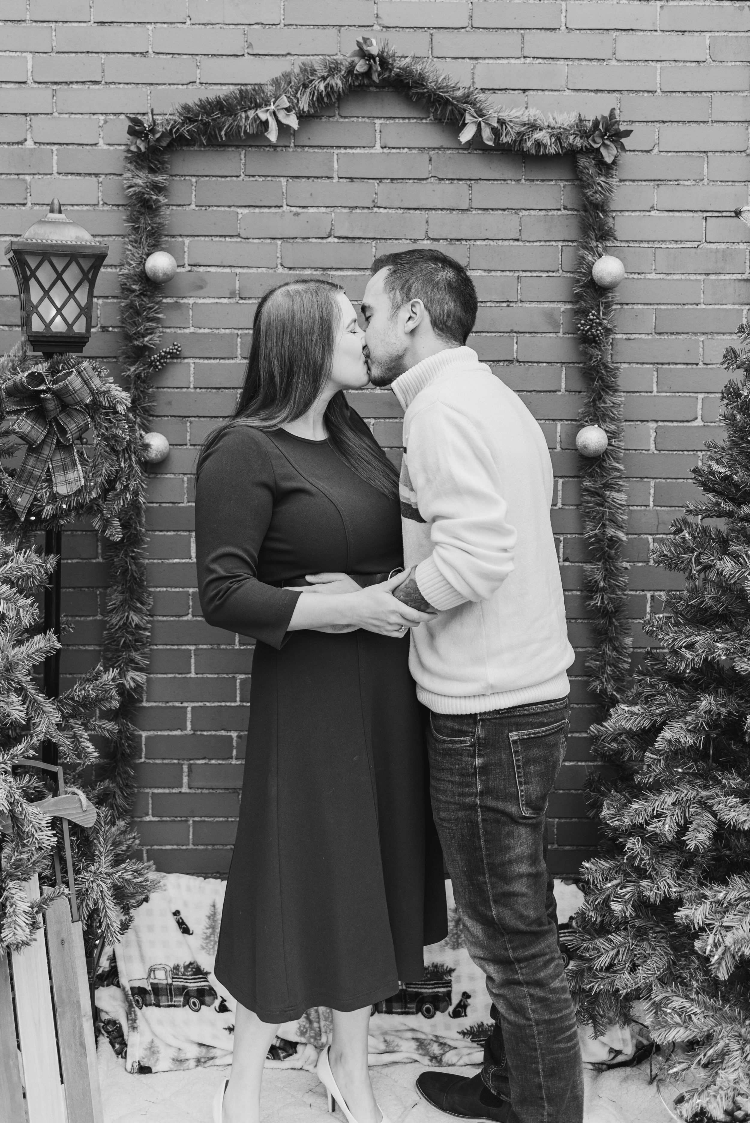 Couple kissing in black and white in holiday Christmas shoot with surprise proposal in Pittsburgh, Pennsylvania