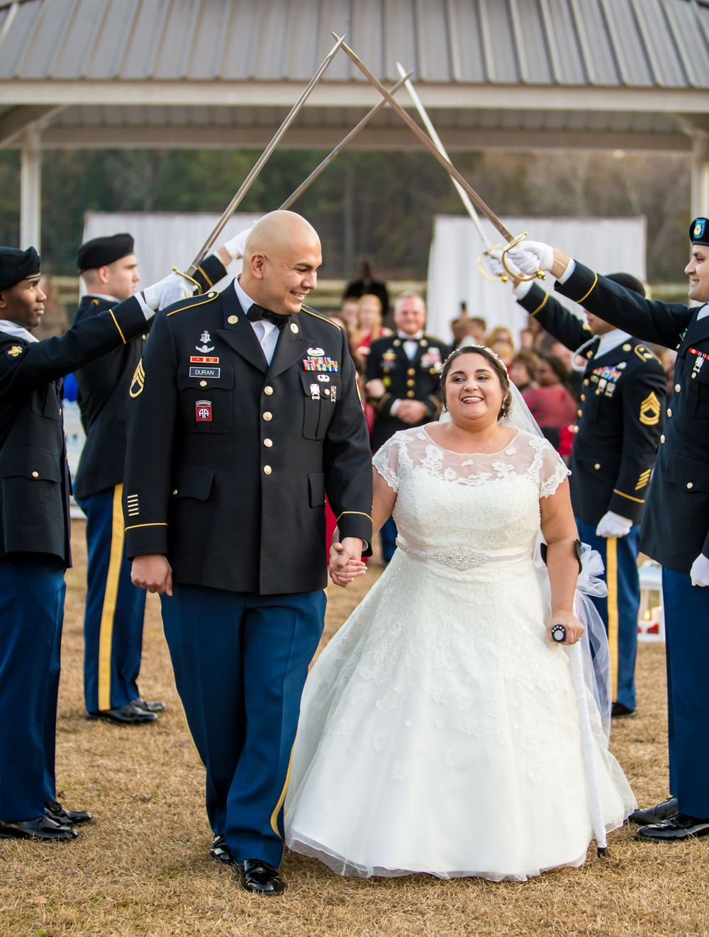 Bride Katie and groom Andrew walk under a saber arch following wedding at the Fort Jackson Officers Club in Columbia, SC