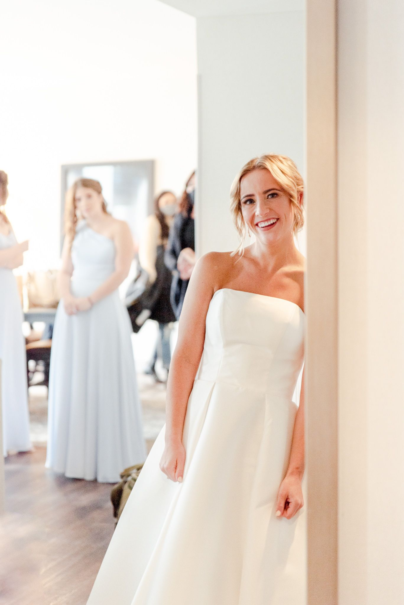 blonde bride with updo smiling at herself in the mirror as bridesmaids watch from the background