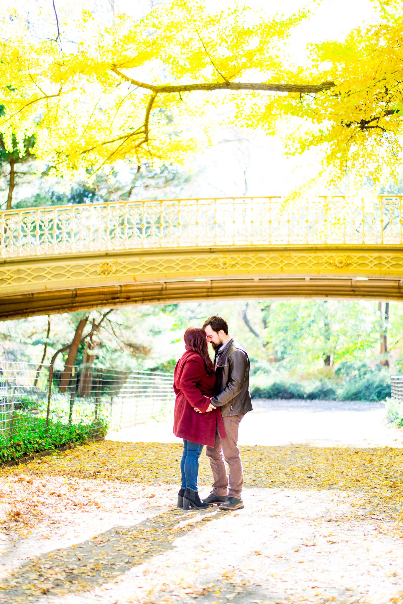 man in brown leather jacket holding hands with woman in red jacket under Pinebank Arch at Central Park in the fall