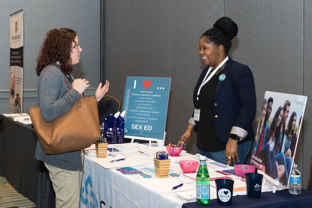 Vendor speaking with a conference attendee.