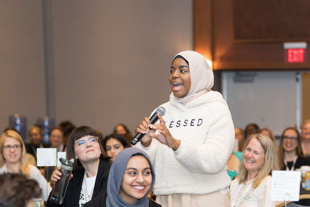 Black female student wearing a hijab speaking at a conference in Detroit.