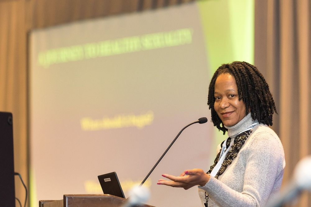 Black woman presenter on stage addressing a crowd of people during Adolescent Health conference.