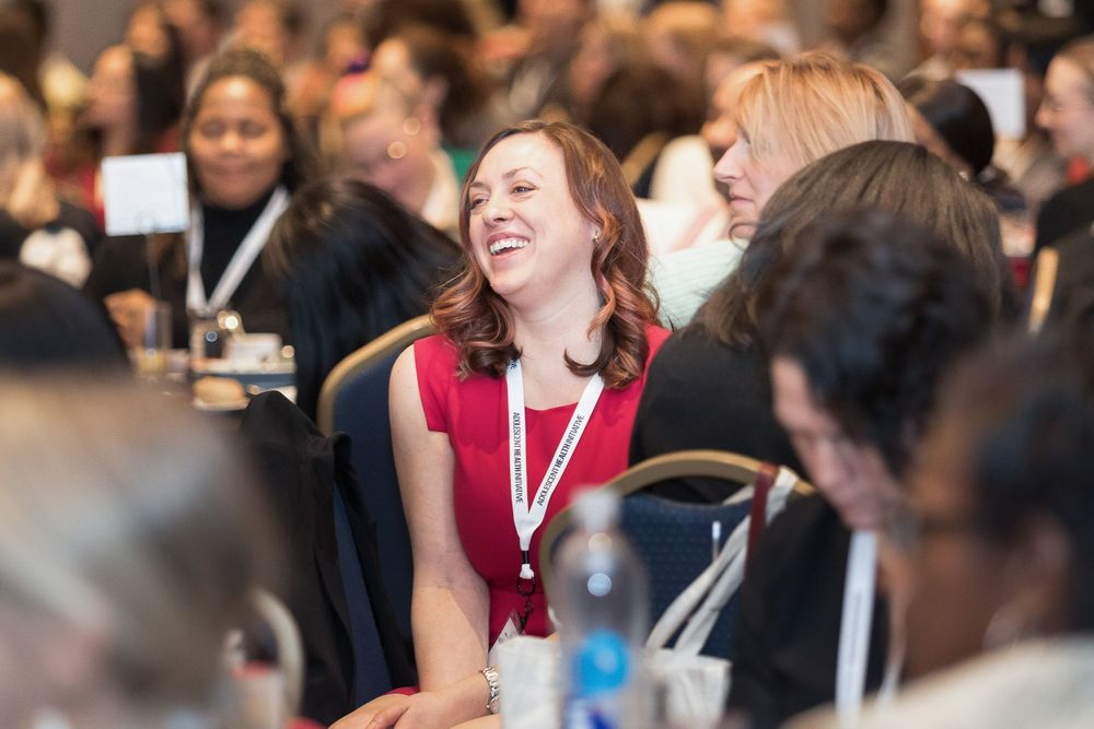 White woman in crowd of people at a conference laughing.