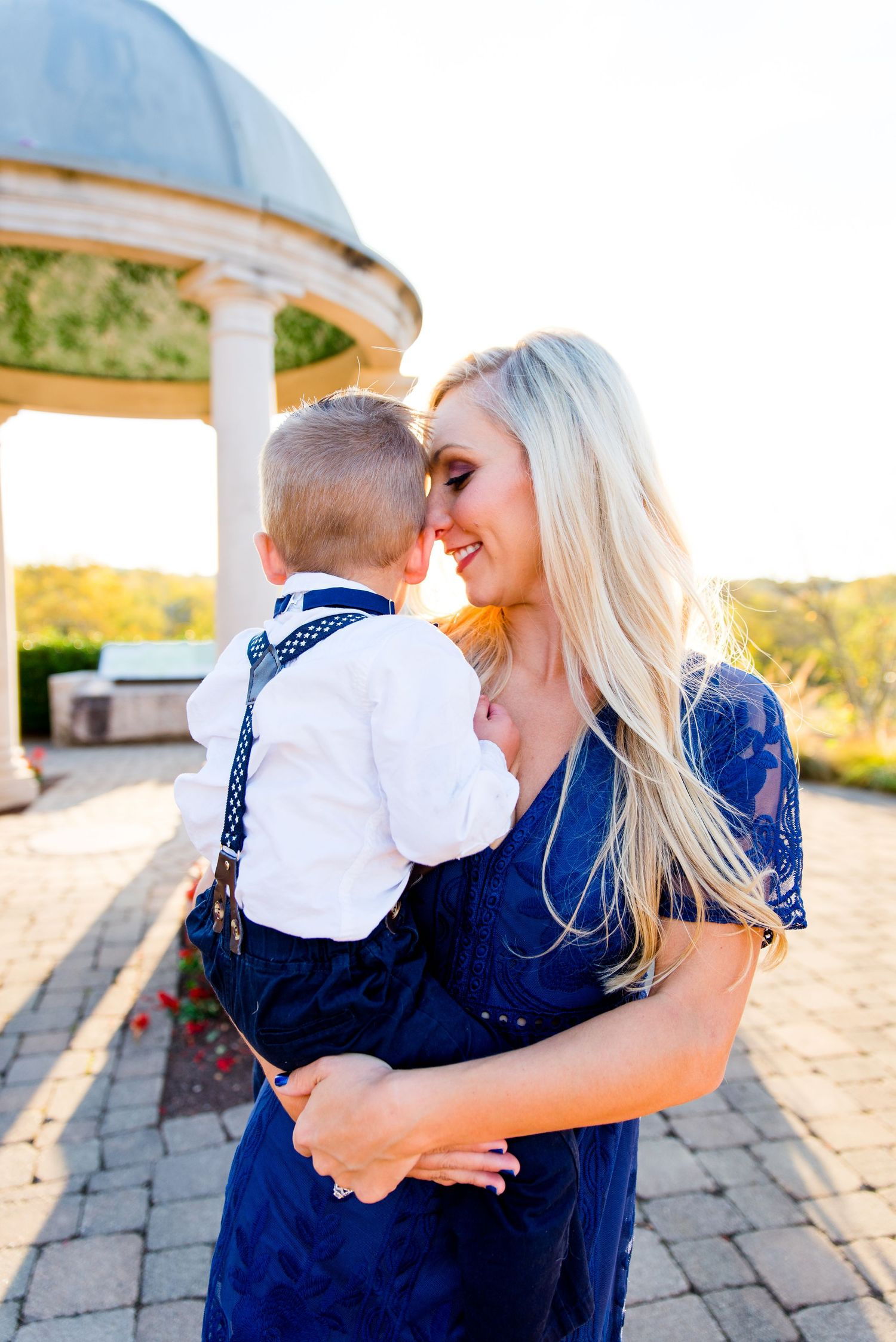 mom with long blonde hair in a navy lace dress putting her nose on her young baby son's cheek