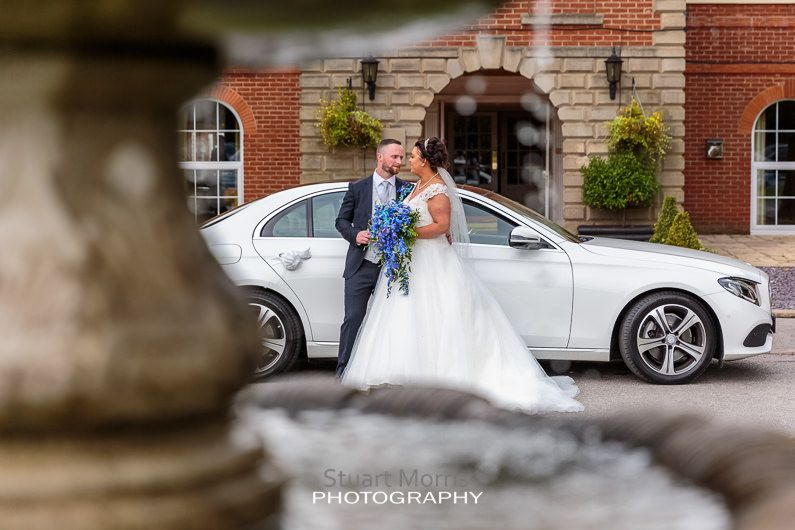 portrait of the bride and groom standing by their wedding car outside the haydock mercure hotel