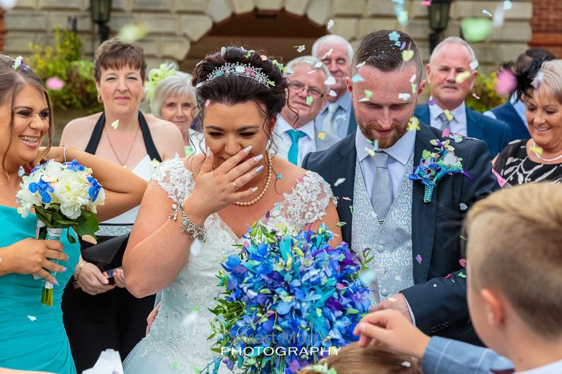 bride puts her hand to her mouth laughing during the confetti throw
