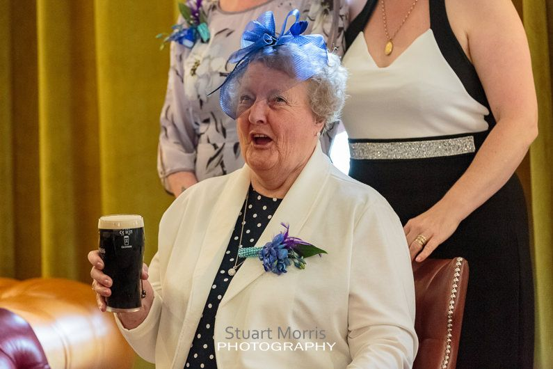 elderly lady sits down and enjoys a pint of guinness at the drinks reception