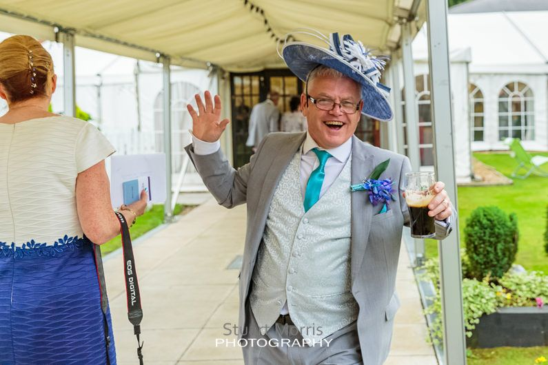 brides father wearing his wife wedding hat poses for a photograph in the grounds at the mercure hotel haydock