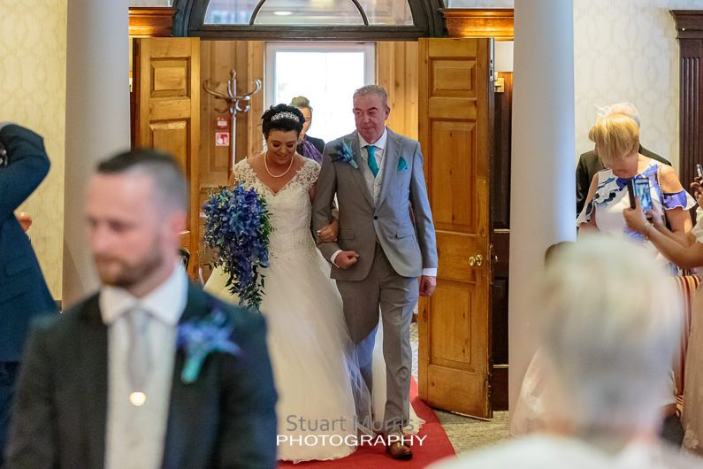 bride enters the ceremony room at the mercure hotel haydock arm in arm with her father
