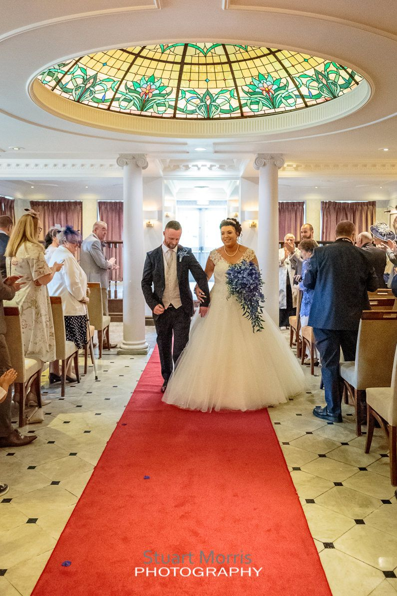 bride and groom walk back up the aisle under the stained glass domed roof at the mercure hotel haydock