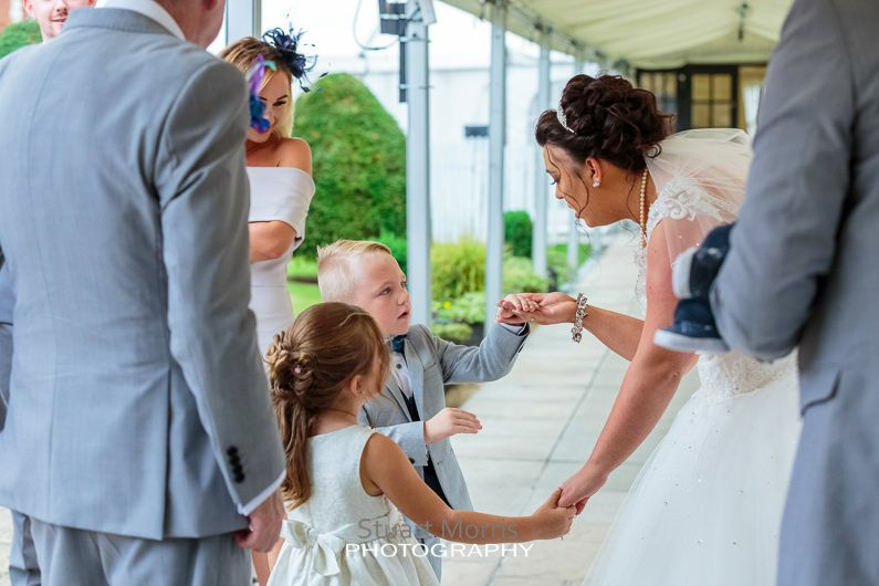 the bride bends down to talk to a little girl and boy in the gardens at the mercure hotel haydock