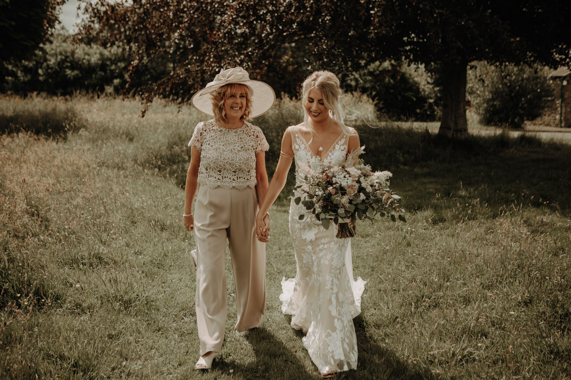 Mother of the Bride and bride, made with love gown and sassflower bouquet, cumbria wedding
