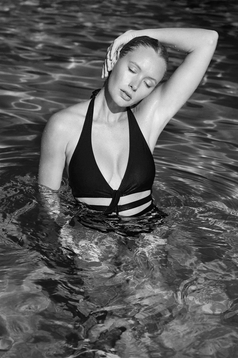Model Carley Johnston standing in swimming pool one piece swimsuit black and white south beach miami timeless