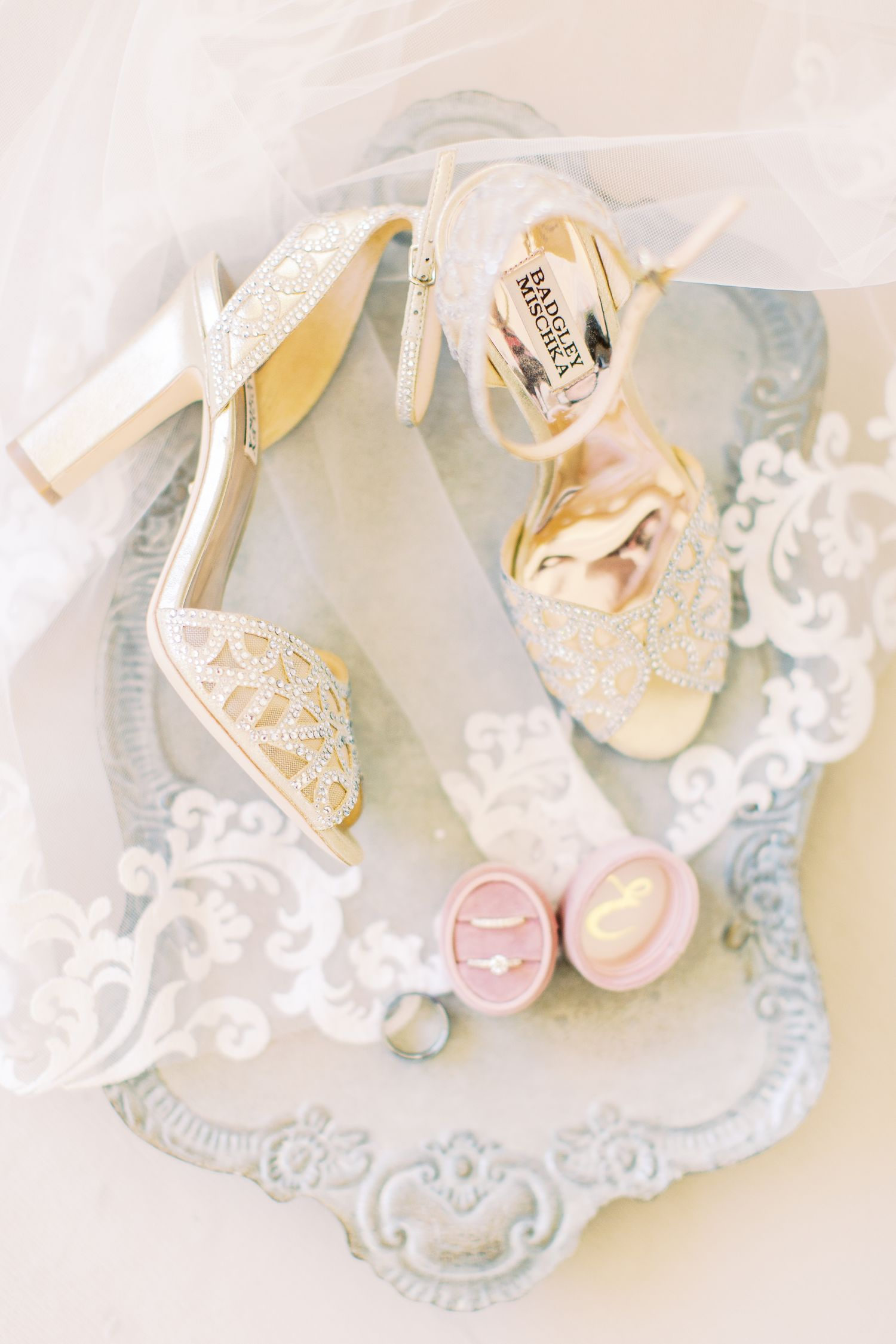 wedding details of badgley mischka shoes and wedding ring on a veil dripped tray