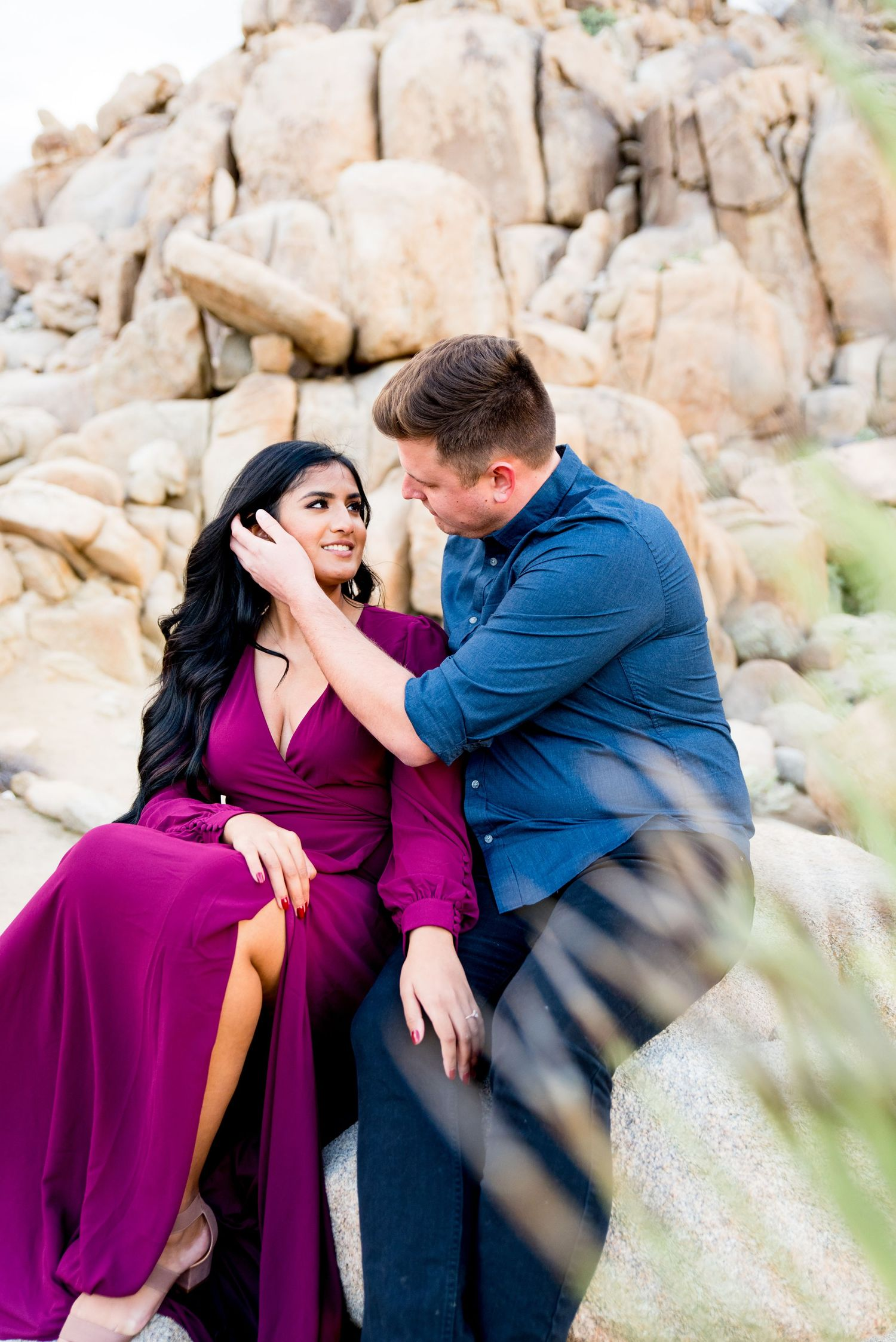 man in blue button down puts hand on face of woman with long dark hair in a red dress at Joshua Tree Park in California