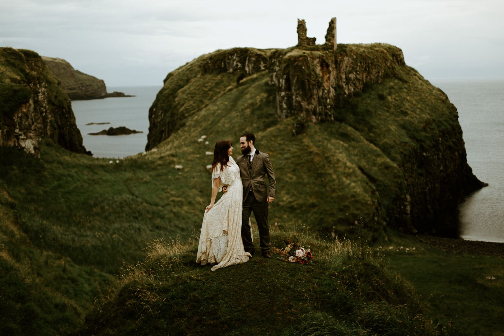 Couple eloping at Dunseverick castle in Northern Ireland by the sea on the cliffs wearing a boho wedding dress